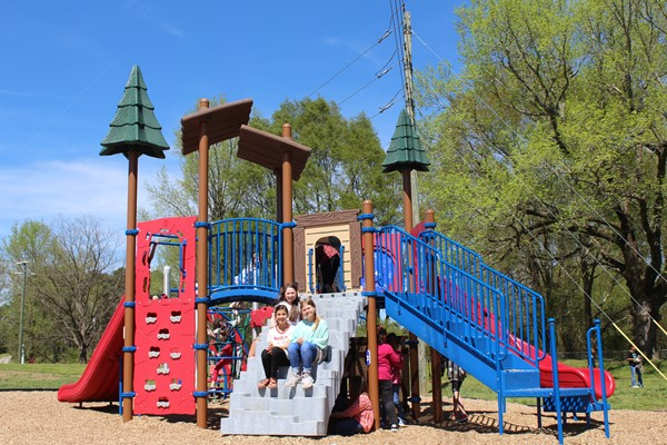 Students playing on the playground. Three sitting on steps of play structure.